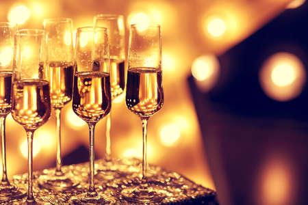 Photo for Transparent wineglasses with champagne placed on blurred background of bright illumination during party - Royalty Free Image