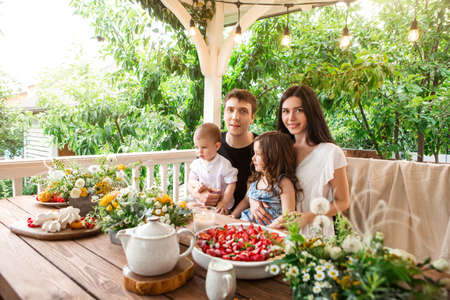 Photo for Loving family with kids sitting at table with delicious desserts and flowers during breakfast in countryside in summer - Royalty Free Image