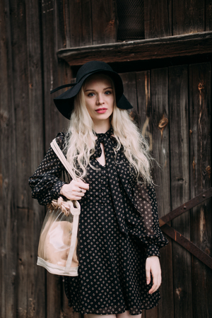 Beautiful attractive and stylish girl wearing black hat standing posing in city. Nude makeup, best daily hairstyle and great fashion glamour country style.