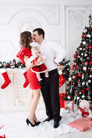 Baby girl wearing cute dress and headband, lies on a white cover in festively decorated room. With surprise watches in the camera, on a background a set of bright fires, soft focus. Warm beige and gold colors