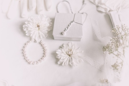 Foto de White bridal accessories for wedding background with pearls, white satin ribbons and lace, gloves, bracelet,flat lay for fashion blog, top view - Imagen libre de derechos