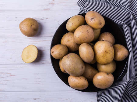 Organic young potatoes raw in black plate on white wooden background