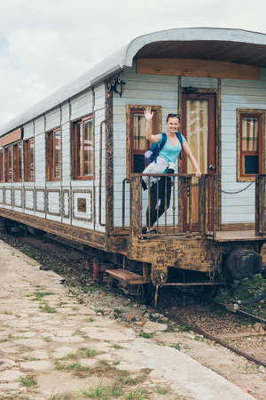 Young woman waving on railway station. Beautiful girl in blue t-shirt with backpack standing in old train wagon. DaLat Railway Station, may 2017