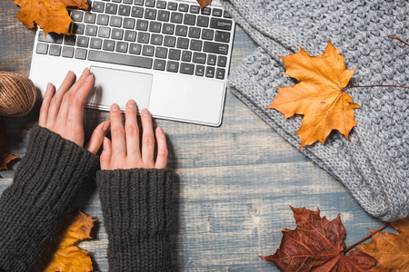 Photo for Workspace with yellow and red maple leaves. Desktop with laptop, fallen leaves on gray wooden background. Flat lay, top view. Woman hands typing - Royalty Free Image
