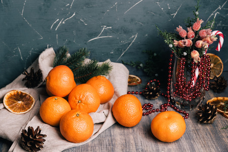 Sweet fresh tangerine on the wooden table. Christmas composition with fir tree brunches, pine cones, berries, candys and dry oranges.