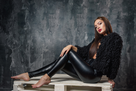 Brunette woman sitting on wooden pallet couch. Sexy female model in elegant black pants and short eco faux fur coat thinking and dreaming