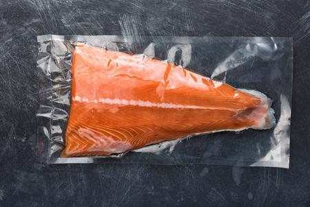 Foto für Salmon fillet packaged in plastic vacuum pack. Fresh fish in packing sell in supermarket. Metal black background - Lizenzfreies Bild
