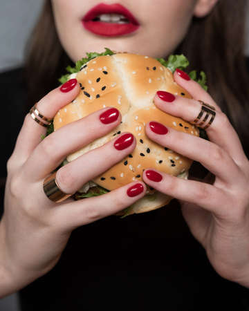 Photo pour Glamor woman with a perfect fashion red manicure and makeup eating burger. Fast food concept - image libre de droit