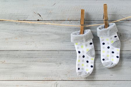 Photo pour Baby socks hanging on clothesline on wooden background - image libre de droit