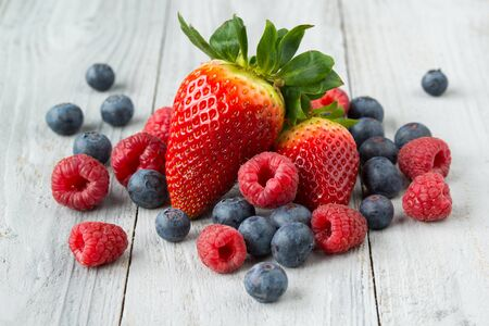 Photo pour Assorted fresh juicy berries on gray wooden background, strawberry, blueberry and raspberry - image libre de droit