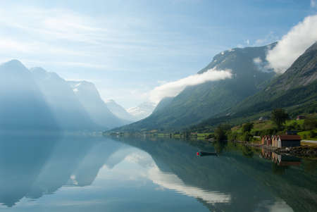 Photo pour Landscape with mountains reflecting in the lake and small boat near the shore, Norway - image libre de droit