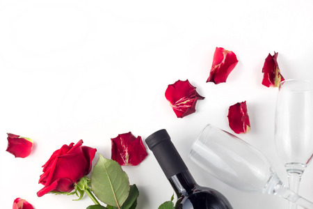 Foto de Bottle of wine, glass and red rose with petals on a white background isolated - Imagen libre de derechos