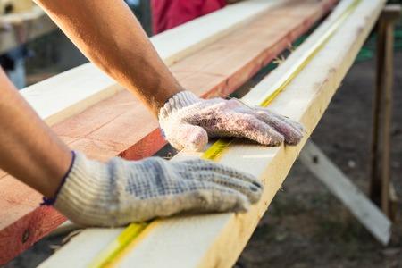 Photo pour Close up view of a man hands measuring wooden plank with a tape line. Measurement. Building and maintenance. - image libre de droit