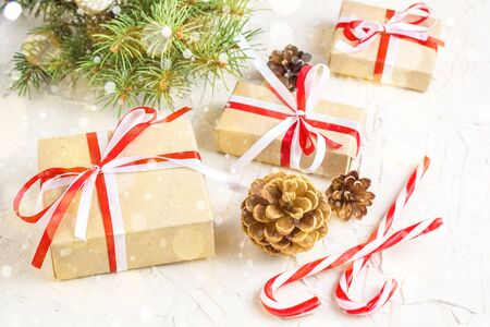 Foto de Christmas or New Year decorations background with pine cones, fir branches, gift boxes, and candy canes. Toned bokeh and snow - Imagen libre de derechos
