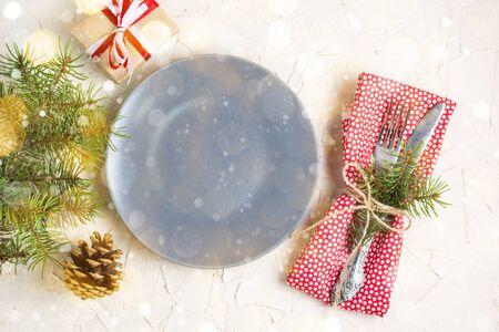 Foto de Christmas table setting with gift grey plate on white table. Xmas concept top view. Toned bokeh and snow - Imagen libre de derechos