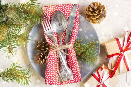 Foto de Christmas table setting with candy cane, christmas tree, pine cones and gift, on white table, top view copy space. Toned bokeh and snow - Imagen libre de derechos
