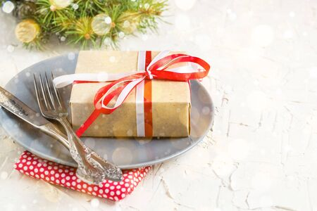Foto de Christmas table setting with gift on plate on white table. Xmas concept top view. Toned bokeh and snow - Imagen libre de derechos