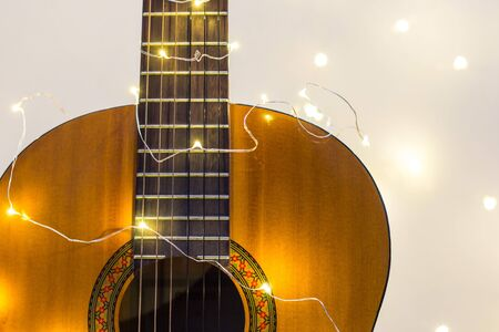 Photo for acoustic guitar wrapped in a luminous garland. Christmas gift with space for text - Royalty Free Image
