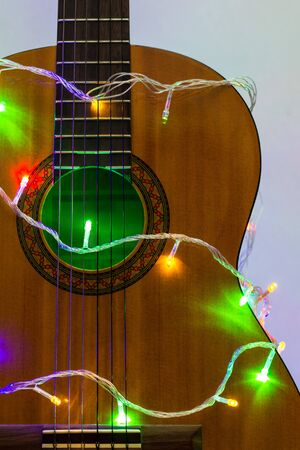 Photo for Acoustic guitar wrapped by colorful garland. christmas and new year music gift as background - Royalty Free Image