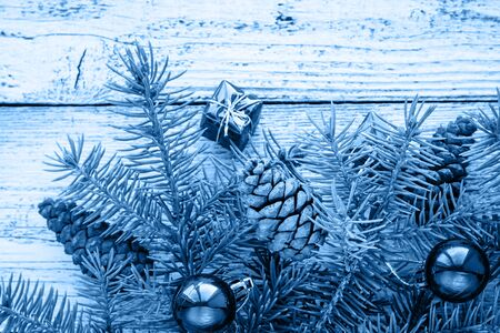 Foto de Christmas accessories in blue, cone and fir branches on wooden white background in classic blue trendy color. Color of the year 2020. - Imagen libre de derechos