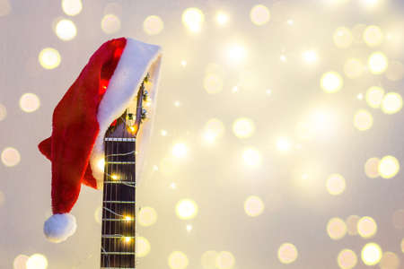 Photo pour Acoustic Guitar with red Santa hat and light garland with bokeh. Christmas music song concept with copyspace on white background - image libre de droit
