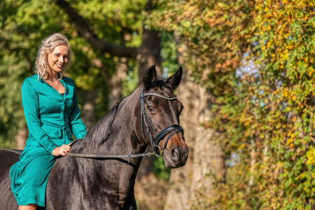 Photo for Portrait of a blonde girl in a vintage green dress with a big skirt posing with a brown horse. Selective focus. - Royalty Free Image