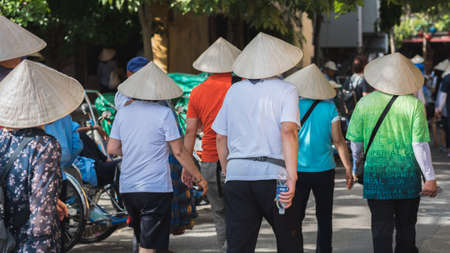 Hoi An, Vietnam - October 23, 2018: group of Asian tourists in Vietnamese conical hats walk in the street, view from behind. The number of Chinese travelers has significantly grown recently in Hoi An.