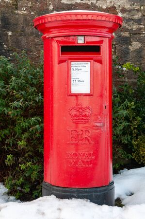 Photo pour A traditional red British Post Box in a snowy rural setting. An old fashioned pillar box with snow on the ground. - image libre de droit
