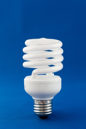 Modern energy saving light bulb on blue background
