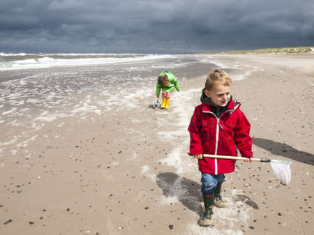 Small children in bightly coloured rain clothes playing with fishing nets in the surf