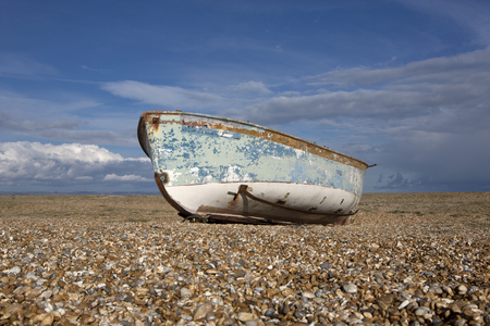 A solitary fishing boat on a shingle beach.