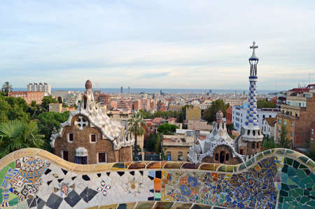 View of the pavilions of the entrance to Parc Guell and undulating bench