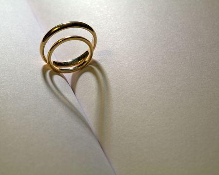 Foto de Two rings that cast a shadow heart on a book - Imagen libre de derechos