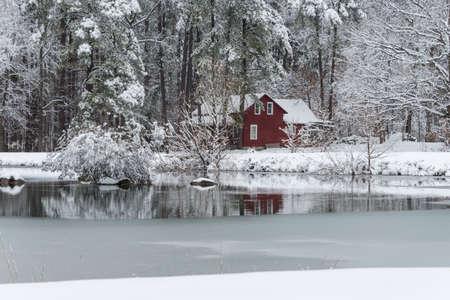 Foto de Red house in snow surrounded by woods behind a frozen pond - Imagen libre de derechos