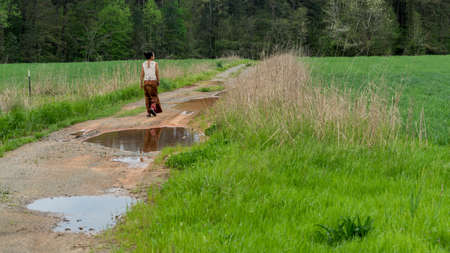 Photo pour Back of woman in sarong walking away  on dirt road with puddles in field - image libre de droit