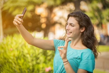 Photo pour Smiling girl taking a selfie with herself behind of green plants - image libre de droit