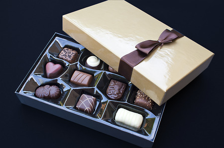 Open golden chocolate box with a brown ribbon