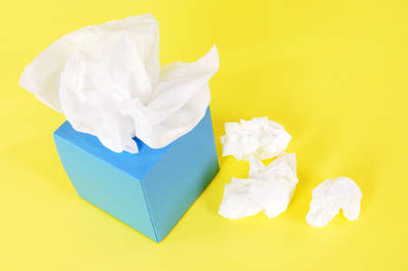 Paper tissues in blank blue box on a yellow background.