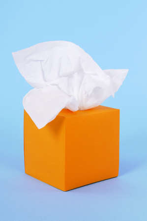 Paper tissues in blank orange box on a blue background.