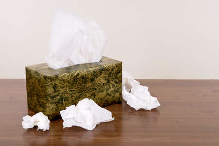 Box of tissues on a wood table .