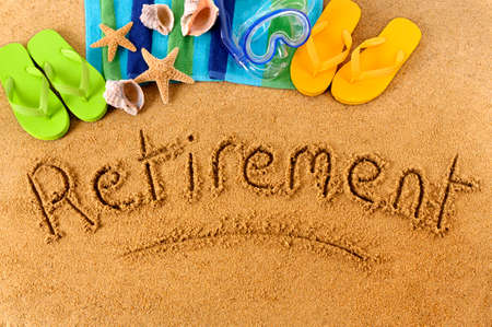 The word Retirement written on a sandy beach, with scuba mask, beach towel, starfish and flip flops.