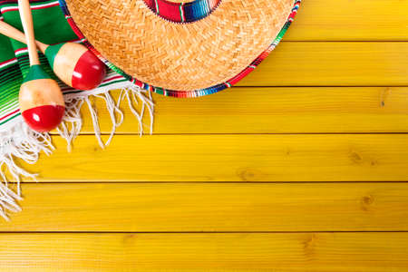 Mexican sombrero, maracas and traditional serape blanket laid on a yellow painted pine wood floor.  Space for copy.