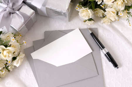Writing paper or wedding invitation with envelope laid on bridal lace with several wedding gifts and white rose bouquets.  Space for copy.
