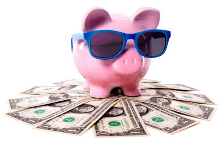 Photo pour Pink piggy bank wearing blue sunglasses and standing on a pile of US dollars.  Isolated. - image libre de droit