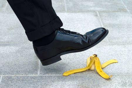 Photo pour Businessman stepping on banana skin - image libre de droit