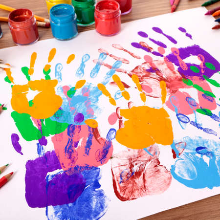 Photo pour Painted handprints with art and craft equipment on a school table.  Shallow depth of field with sharp focus on the nearest handprints and blurred distant background. - image libre de droit