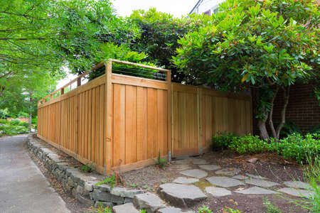 Photo pour New Cedar Wood Fence with gate door on home side yard landscaping - image libre de droit