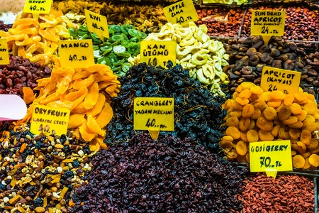 Dry fruits like mango, kiwi, aple, apricot, ranberry, gojiberry, anise, etc  on display in containers for sale in a bazaar, Turkey