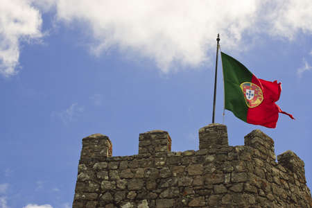 A flag is flying above the stone battlement of an ancient castle tower. Horizontal shot.
