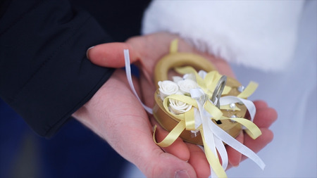 Wedding symbol, lock in hands of bride and groom. Newlyweds fix the lock on the bridge as a symbol of love. Padlock in the hands of the bride and groom. Lock in heart shape on the railing of bridge - a symbol of happy and long married life of bride and gr